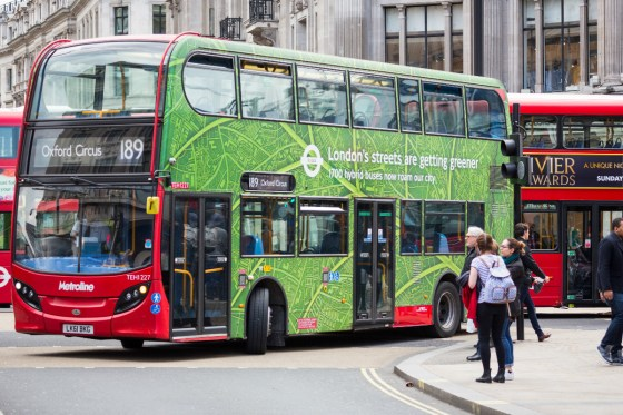 London Bus with green hybrid buses promotion turning Oxford Circus