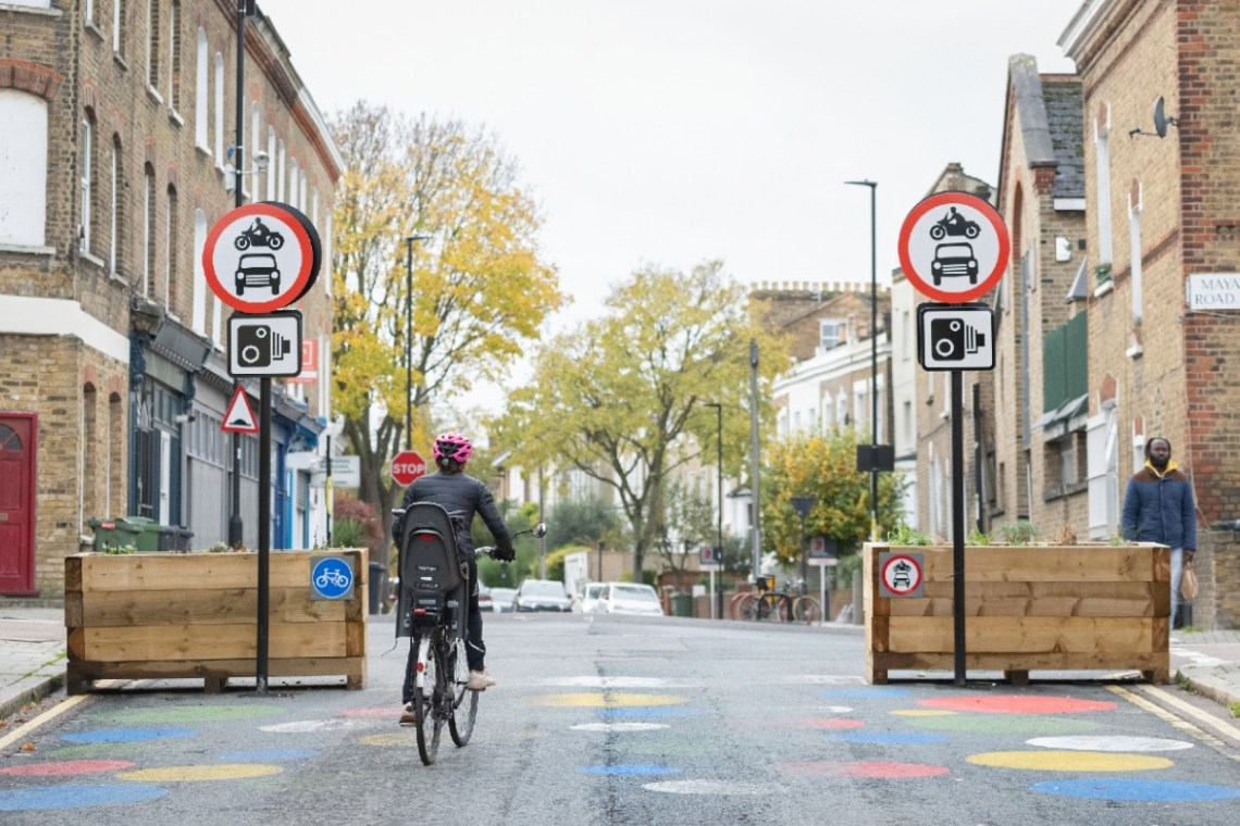Woman and her child cycling past Low Traffic Neighbourhood signs