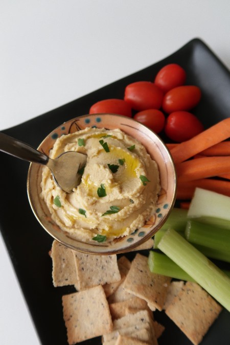 hummus in a small bowl surrounded by a black plate of vegetables and crackers