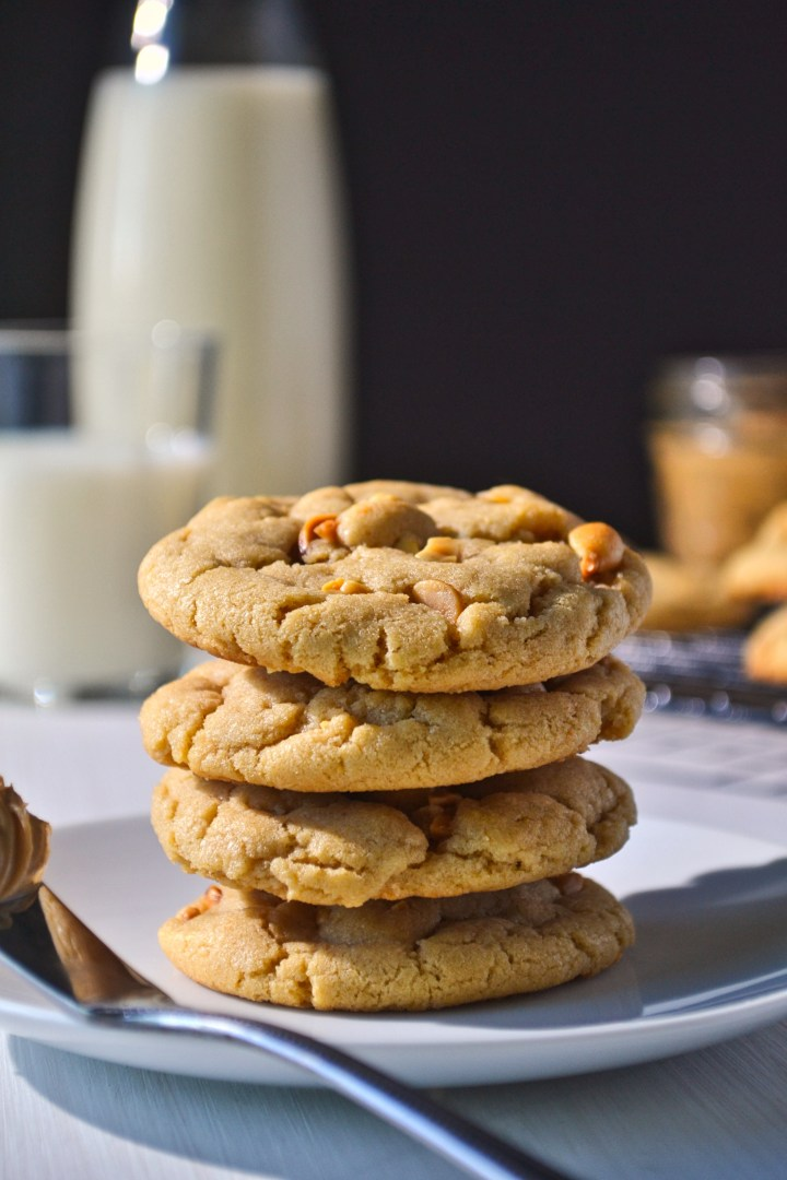 Stack of peanut butter cookies on a plate with a glass of milk and jar of peanut butter in the background
