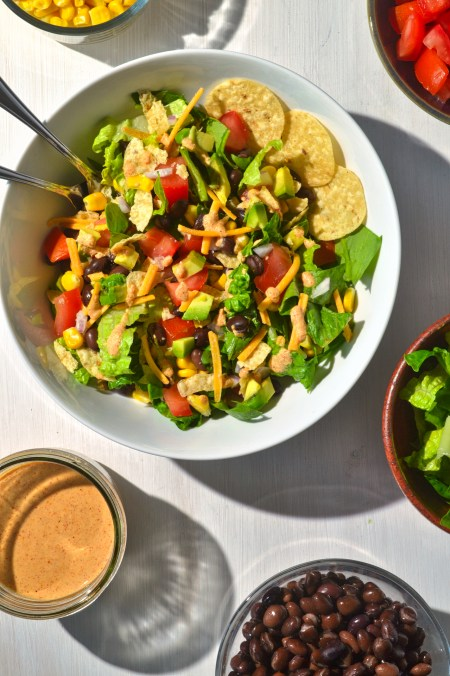 taco salad and two forks in a white bowl surrounded by other bowls with corn, tomatoes, lettuce, black beans, and spicy cashew sauce on a white wooden background