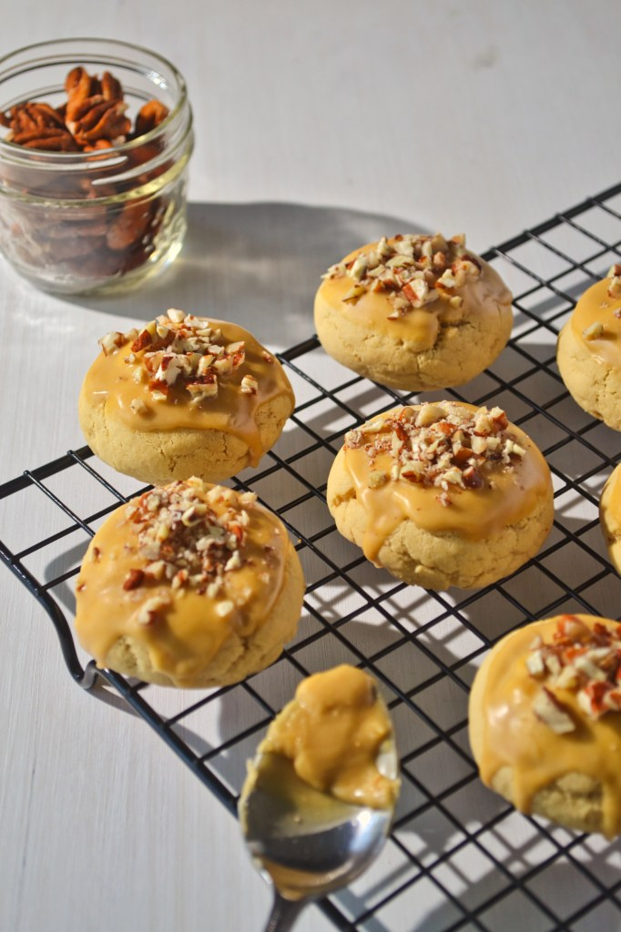 round maple cookies dipped in a maple glaze topped with crushed pecans on a black cooling rack beside a jar of whole pecans