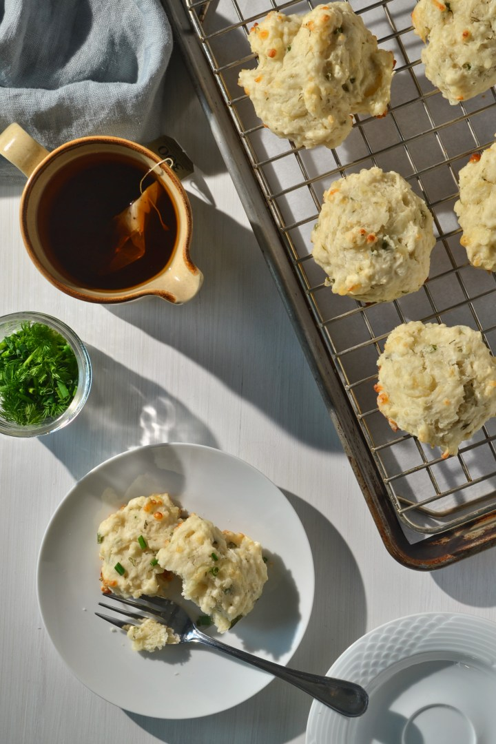 mozzarella herb biscuits on a cooling rack and baking sheet beside a mug of tea