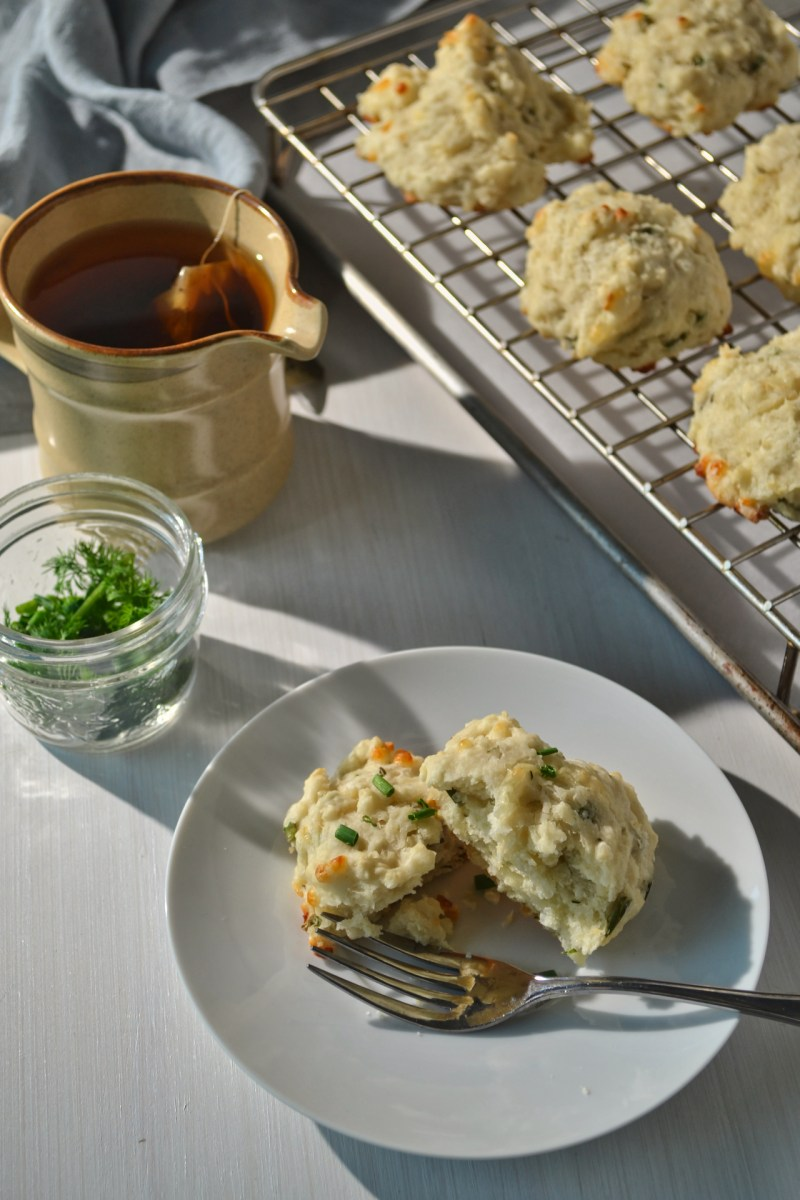 plate with a biscuit on it beside a mug of tea