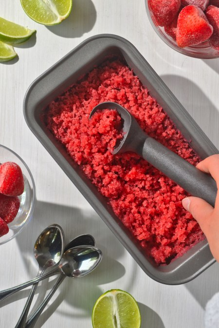 strawberry lime granita in a loaf pan surrounded by spoons, limes, and frozen strawberries