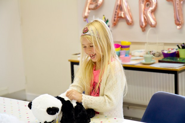 Teddy bear making party by Made by Me Craft Parties. Girl stuffing teddy bear panda with bear stuffing