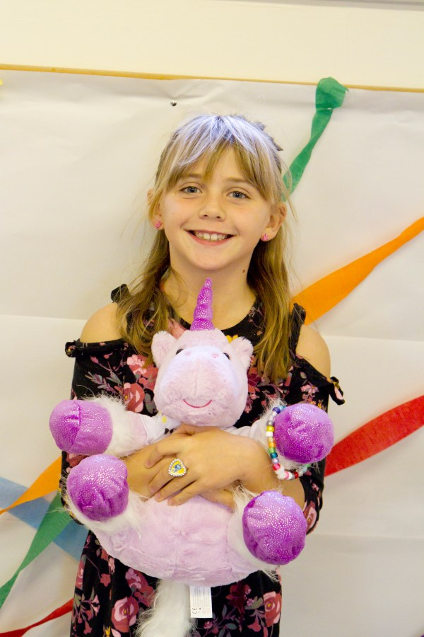 Girl holding unicorn teddy at party
