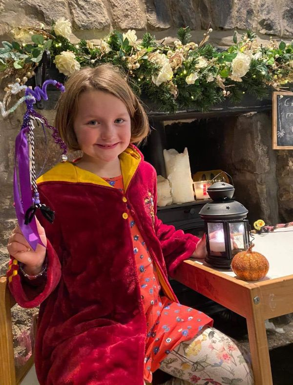 Girl dressed as witch with handmade purple wand