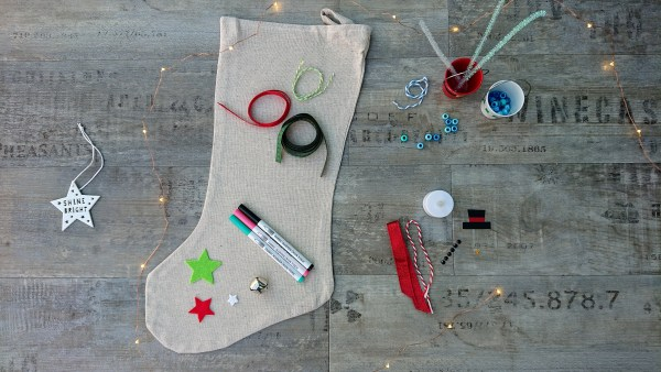 Christmas craft kit contents - ribbons, beads, pipe cleaners, fabric pens and a Christmas Stocking