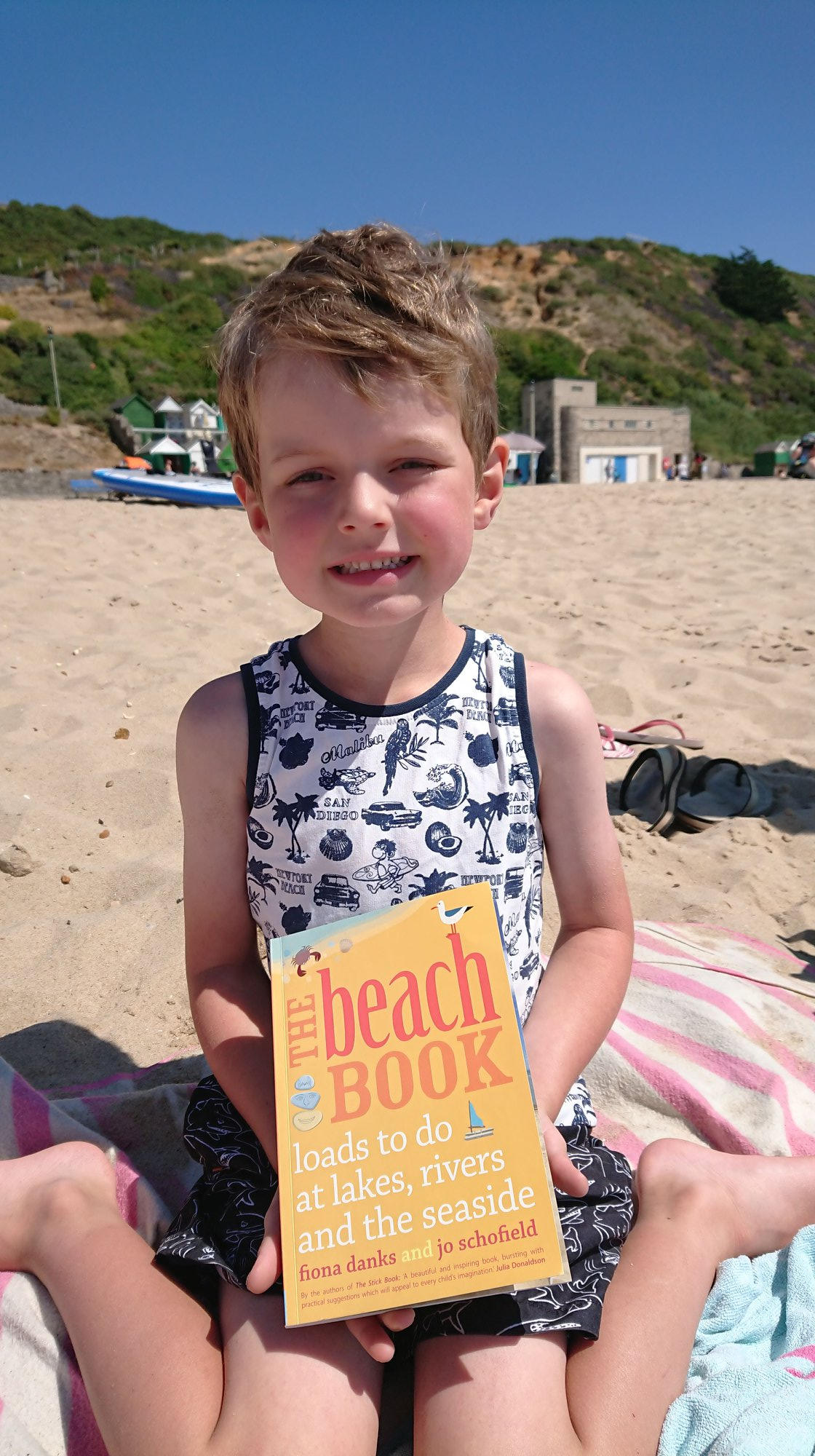 easy summer crafts for kids - boy on a beach holding a yellow book