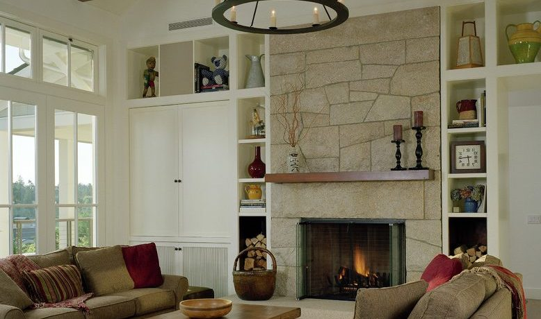 stacked stone fireplace design with bronze candleholders and