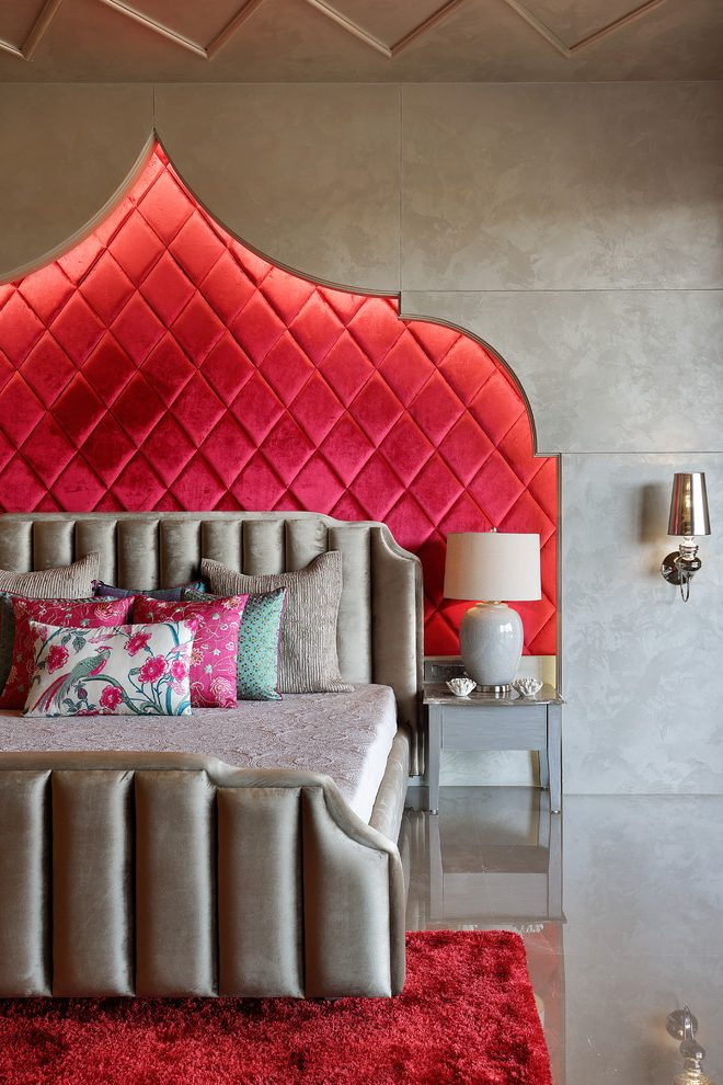 Fabulous camelback upholstered headboard in with floral accent pillows and wall sconce