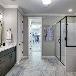Blooming marble for bathrooms in with wall sconce light and Shaker cabinets