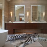 Impressive silver cowhide rug in with bathroom mirror and double sinks