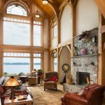 Pretty fireplace stacked stone in with and ceiling to floor windows