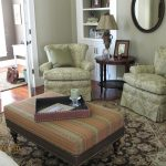 Square Rug And Upholstered Ottoman Coffee Table Brown Walls Builtin Bookshelf Club Chairs Fabric Ottoman French Door Living Room Oriental Rug Square