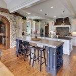 Wooden Bar Stools And Stacked Stone Accent Wall Arched Glass Door Built In Stacked Ovens Industrial Pendant Lights Kitchen Sink Island With 2 Islands