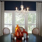Newburyport Blue   Plantation Shutters And Navy And Orange Crystal Chandelier Navy And Orange Newburyport Blue Plantation Shutters Round Dining Table White Wainscoting Windsor Smith Fabric