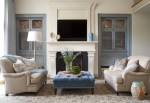 Beautiful Curved Tufted Sofa Living Room Transitional with TV Over Fireplace Glass Tile Ceramic Stool Ottoman Metal Grids Blue Cabinets Limestone Transitional Design Glass Cabinet