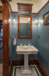 Splendid Powder Blue Paint Color Powder Room Craftsman with Wood Molding Penny Tile Floor Vertical Mirror Beige Wall White Baseboard Sconce Pedestal Sink