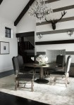 Dishy Black Deer Head Dining Room Contemporary with and White Striped Wall Crystal Chandelier Fireplace Upholstered Dining Chair Centerpiece Table Metal Vaulted Ceiling