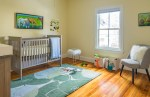Glorious Yellow and Grey Nursery Nursery Transitional with White Fluffy Foot Stool Walls Toy Storage Medium Wood Flooring Green Area Rug Changing Table Gray Chair Crib