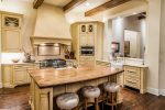 Dishy Vintage Brass Bar Cart Kitchen Rustic with Dark Wood Beams Apron Front Sink Tufted Stools Backless Backsplash Behind Stove Beige Cabinets Glass