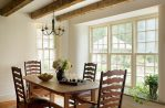 Good-looking Wrought Iron Room Dining Room Farmhouse with Dining Chairs Centerpiece Exposed Beams Floral Arrangements Salvaged Beams Antique Chandelier Beam Ceiling Window Seat Distressed Wood