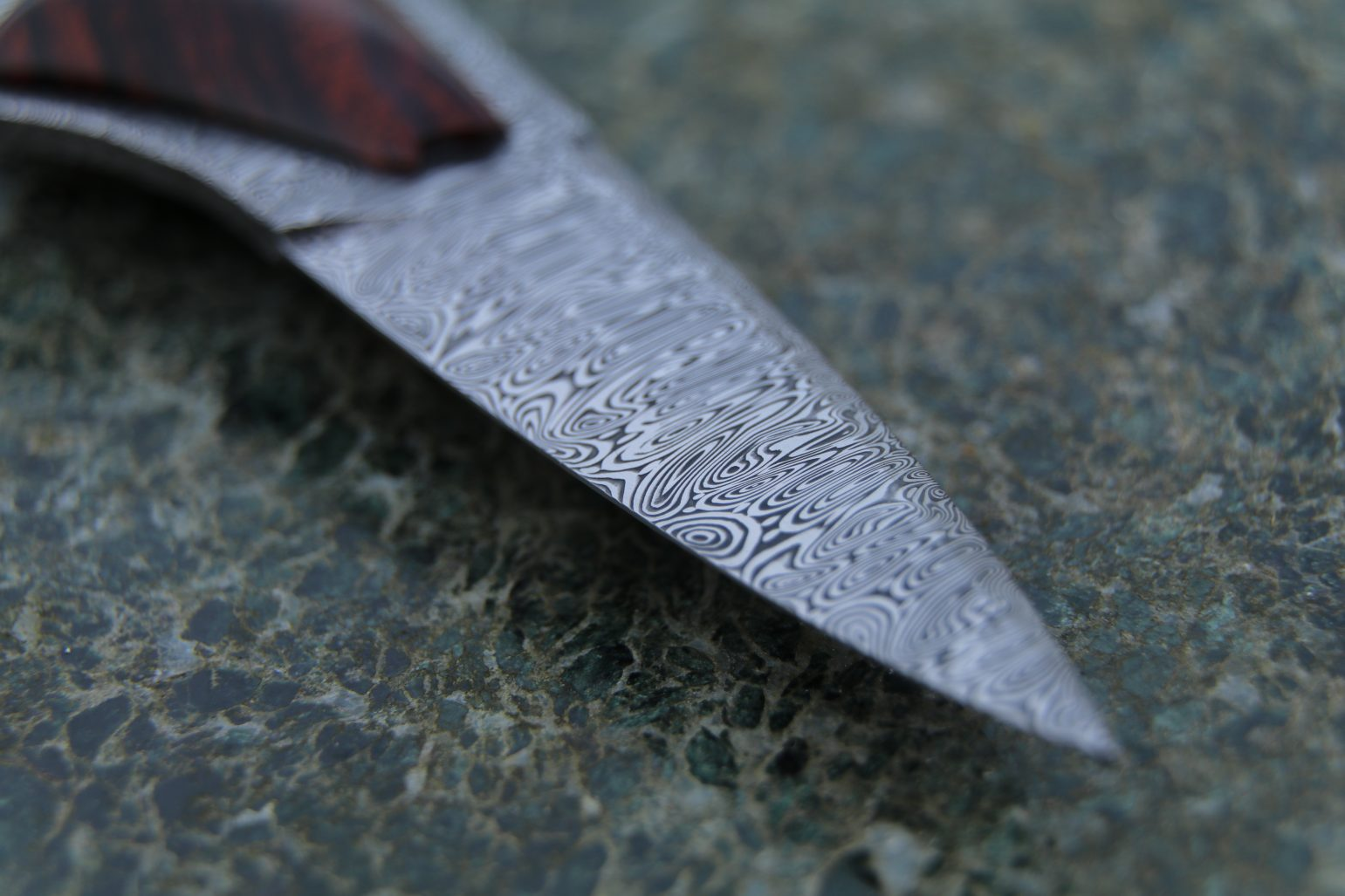 Damasteel Odinheim oyster shucker on a granite slab.