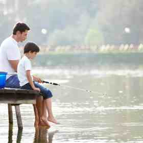 Father sitting and fishing on a dock with his son. Get our list of amazing gift ideas that EVERY father will love. Discover more parenting hacks and family lifestyle inspiration by following Made In A Pinch on Pinterest!