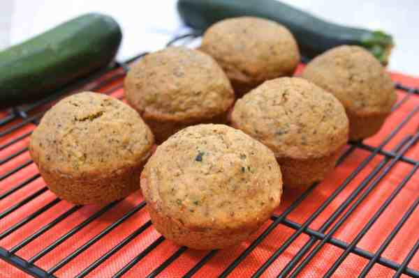 zucchini muffins with fresh zucchini in the background