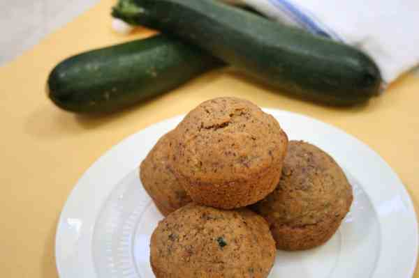 zucchini muffins with fresh zucchini in the background