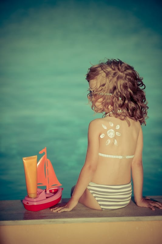 little girl with a sun drawn on her back in sunscreen - find the best sunscreen for kids with these tips