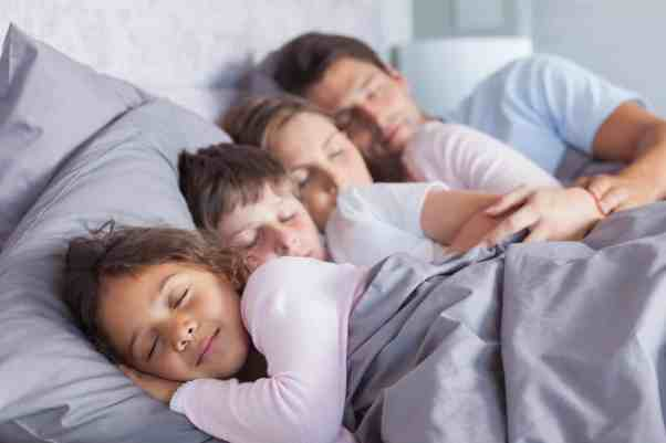 Developing great family sleep habits helps the whole family sleep better and feel great! Get simple tips for better sleep habits at Made In A Pinch. Family of 4 sleeping in a bed.