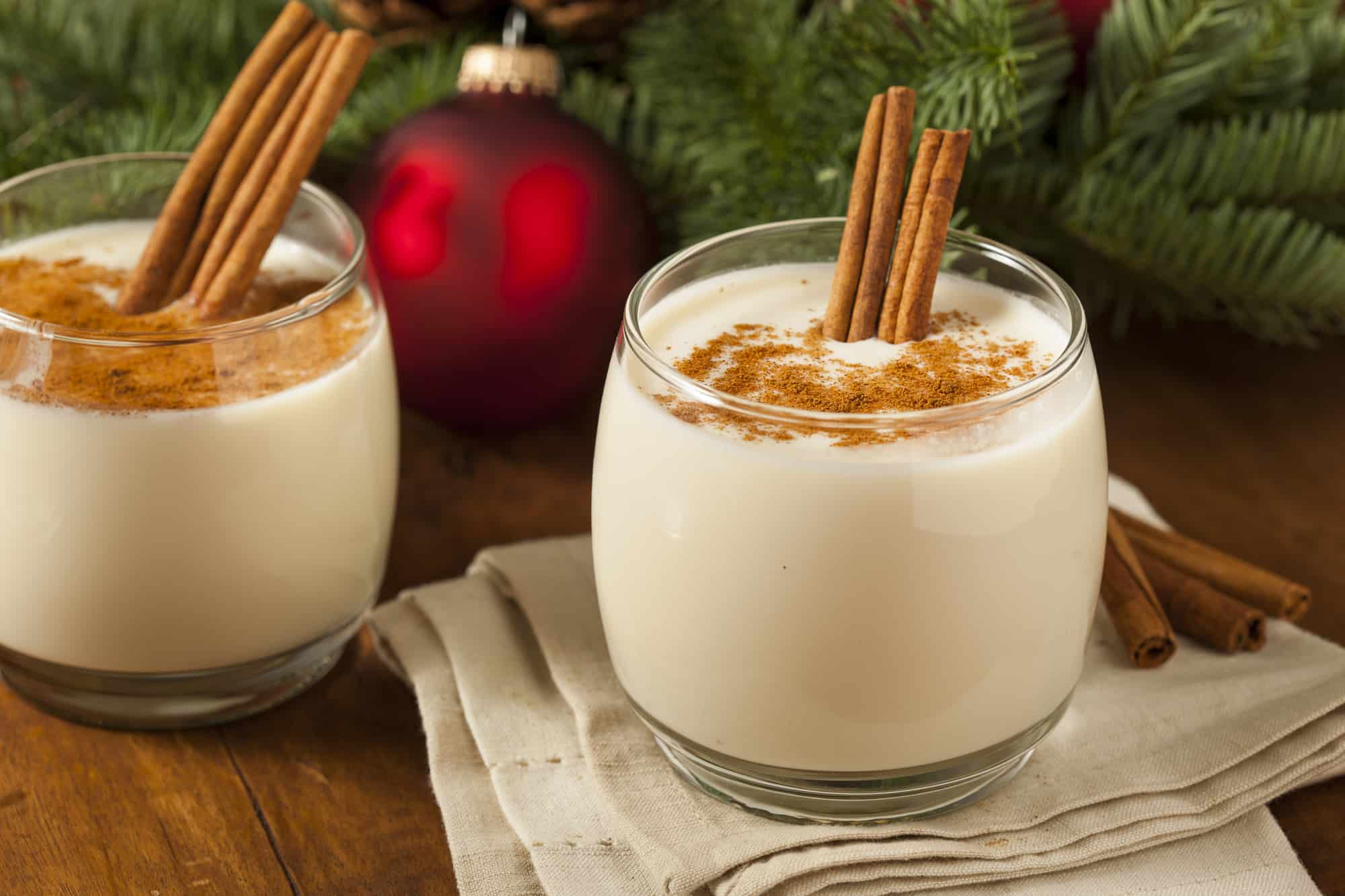 Two glasses of decadent, creamy non-alcoholic eggnog with cinnamon sticks and Christmas decorations