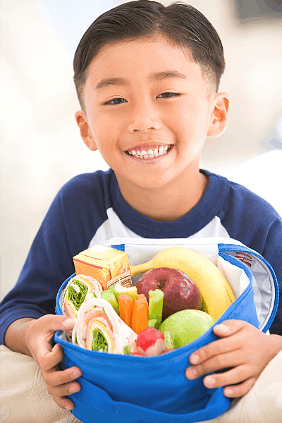 Little boy holding a lunch box packed with a healthy school lunch
