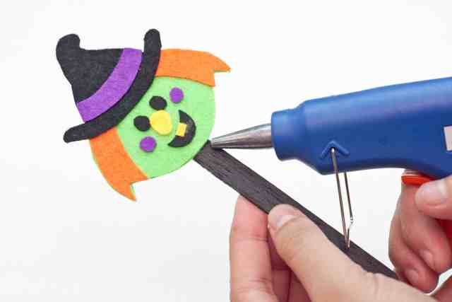 Witch Halloween bookmarks craft for kids tutorial, hot gluing the witch's head to the popsicle stick