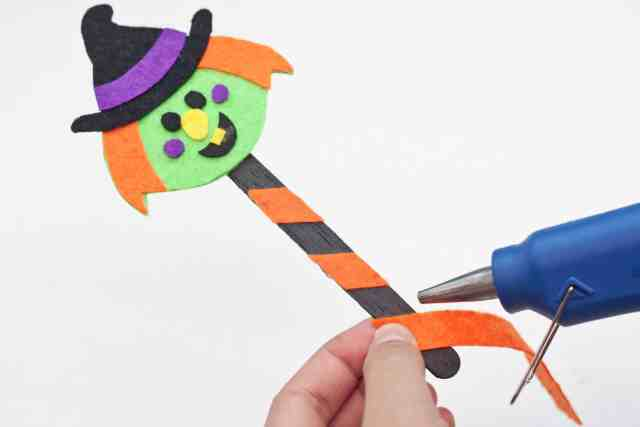 Witch Halloween bookmarks craft for kids tutorial, adding orange diagonal strip to popsicle stick