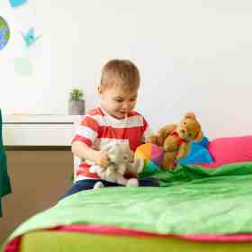 little boy playing with stuffed animals by his bed