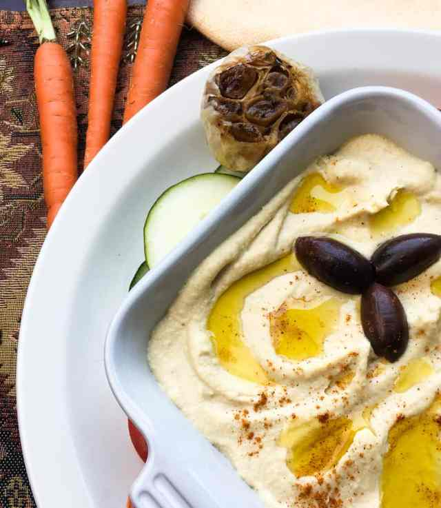 roasted garlic hummus in a bowl topped with a drizzle of olive oil and 3 kalamata olives
