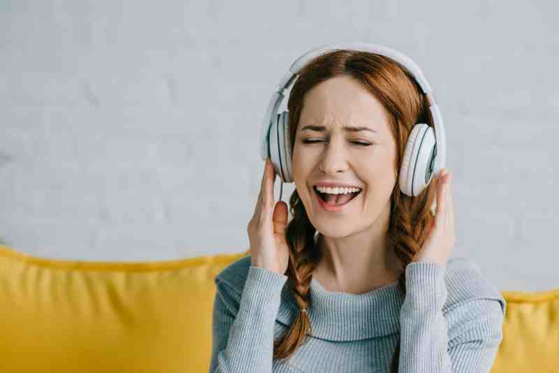 woman sitting on a couch listening to headphones and laughing