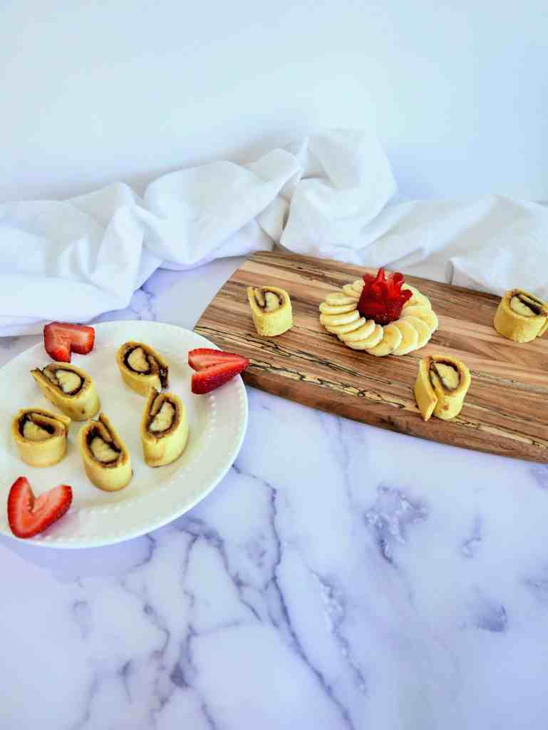 banana & peanut butter sushi rolls on a plate and wooden board