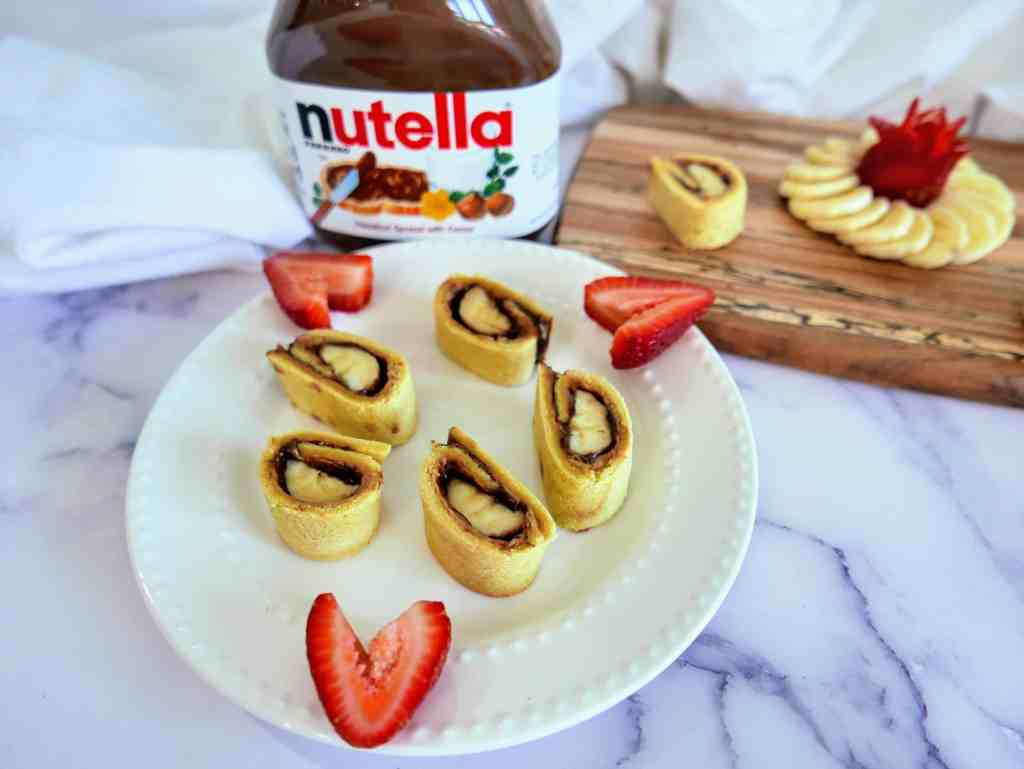 banana, peanut butter, Nutella sushi on a plate with cut up strawberries