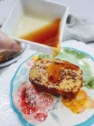 close up of pouring syrup onto a slice of pumpkin french toast