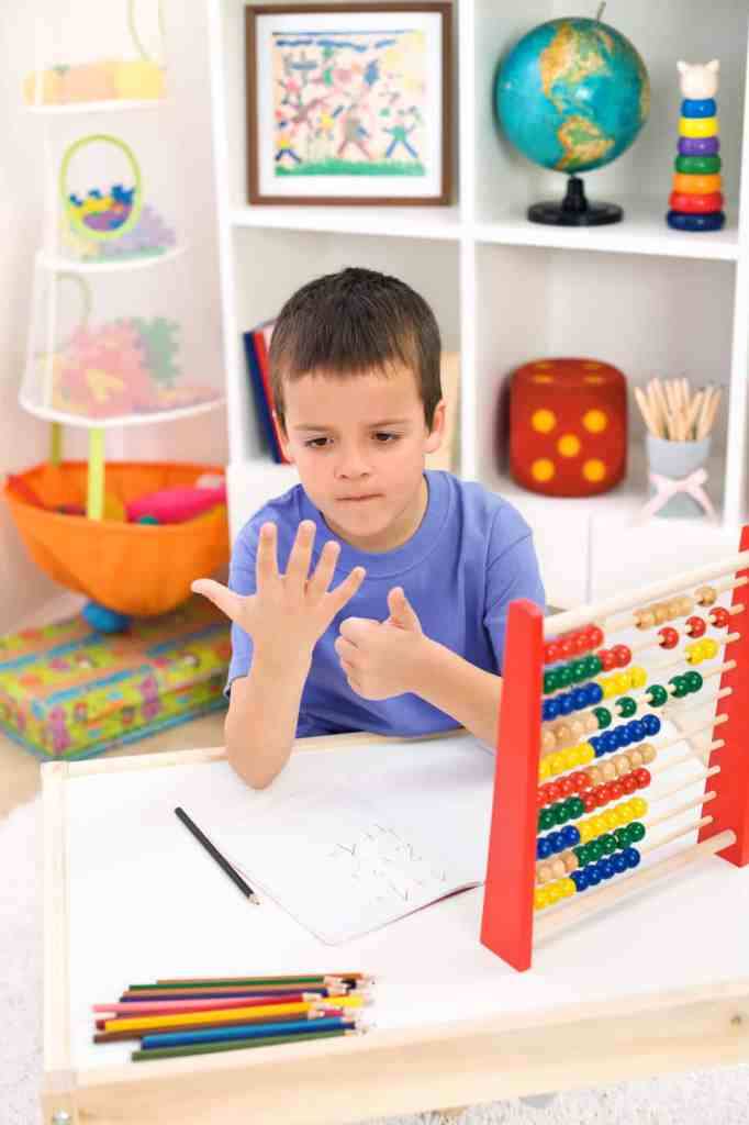 boy working on remote learning by counting on his fingers at home