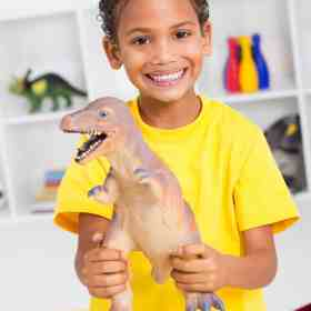 happy toddler playing with dinosaur toys