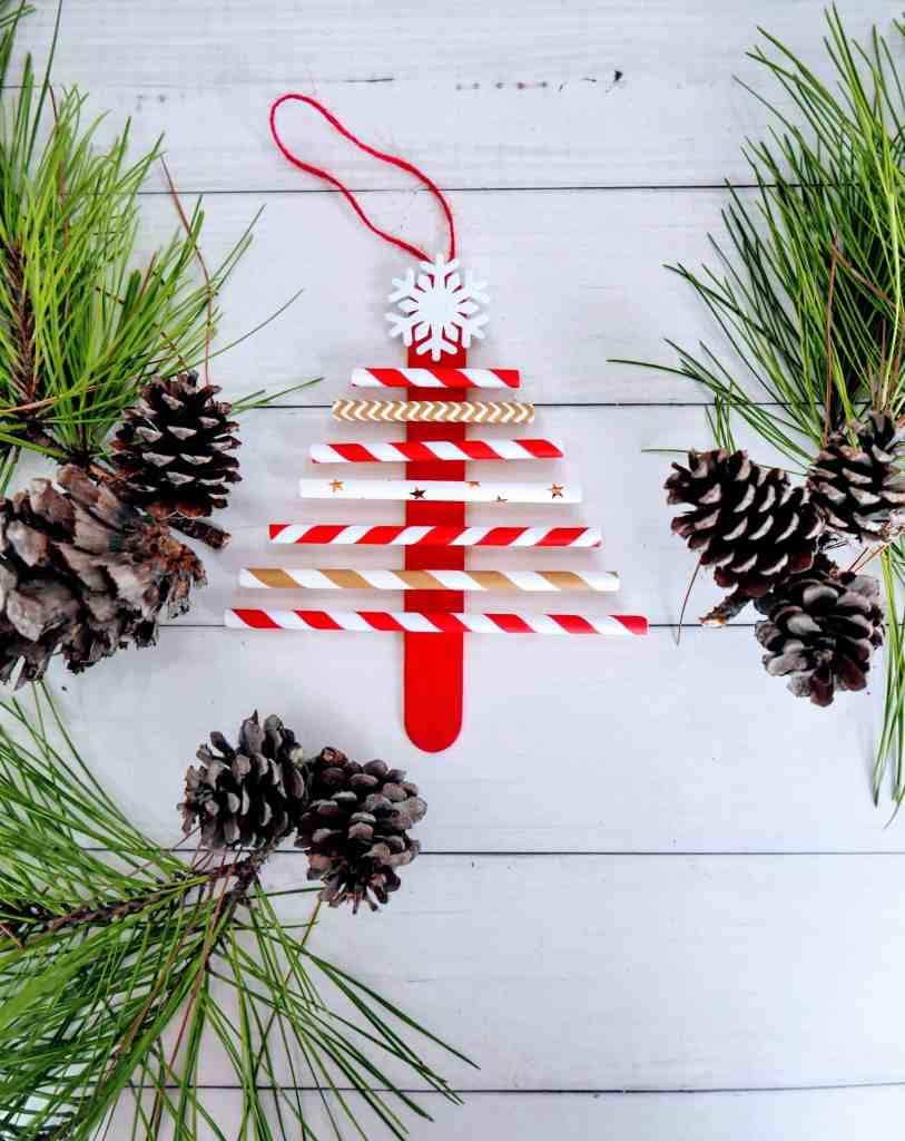 paper straw Christmas tree craft on a table with greenery
