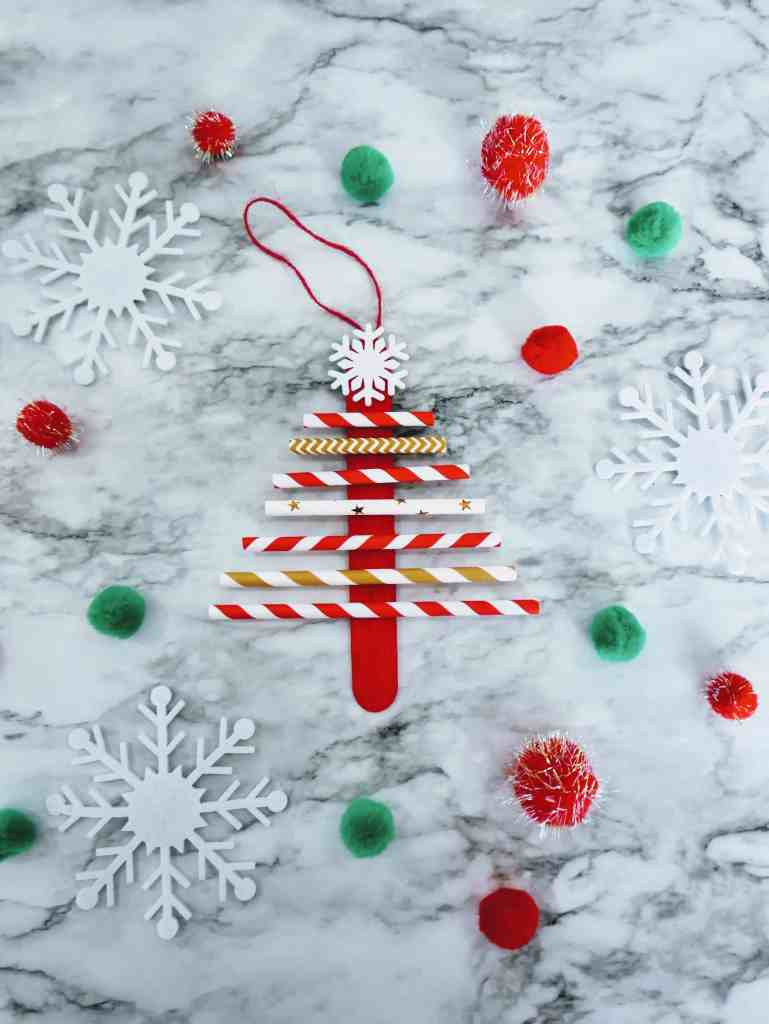 paper straw Christmas tree craft with poms and snowflakes.