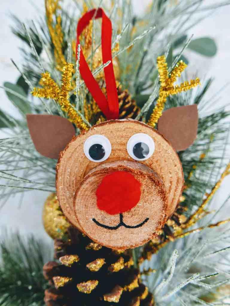 DIY Rudolph wood slice ornament against evergreen