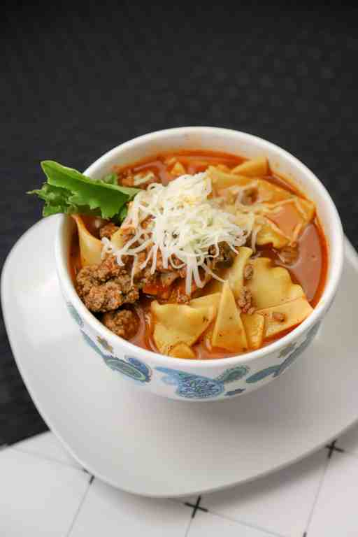 Lasagna soup made in the instant pot in a bowl with a spoon and a side salad